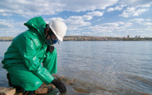 Technician in protective suit taking water samples from city reservoir